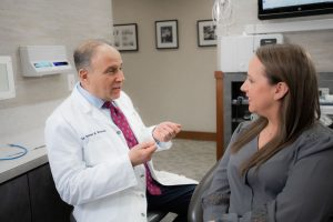 Dr. Brisman, a Chappaqua Dentist, talking with a patient about the dental procedures we offer